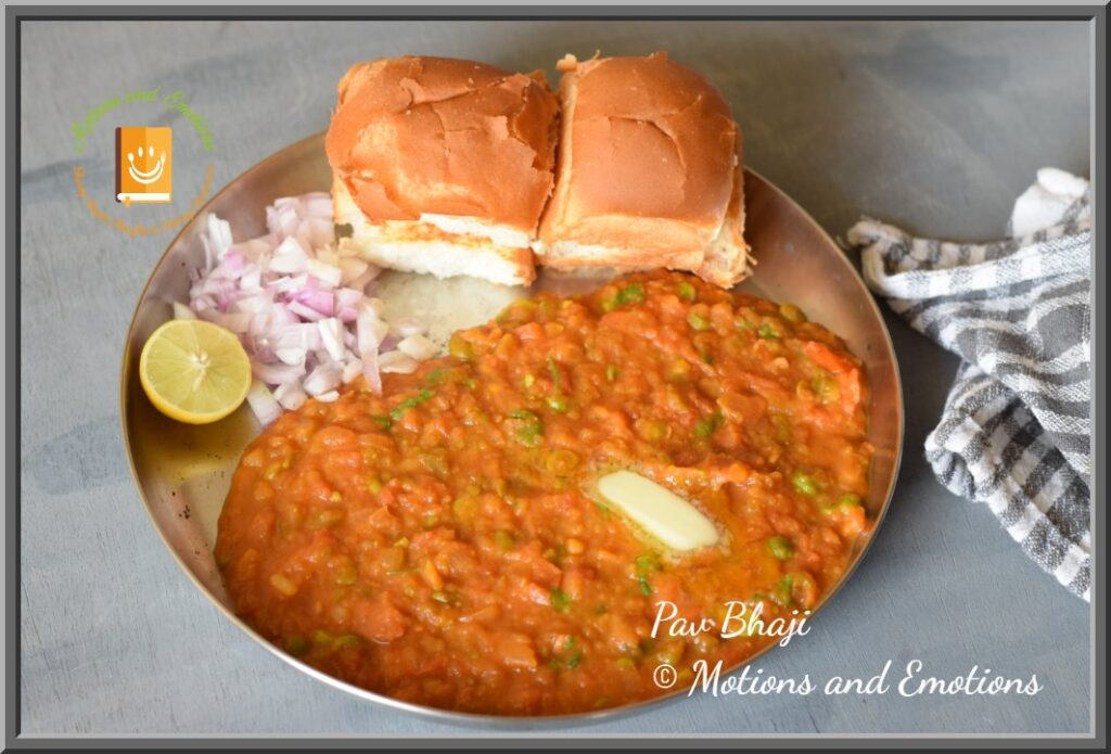 Pav Bhaji served on a steel plate with a dollop of butter, chopped onion and lemon wedge