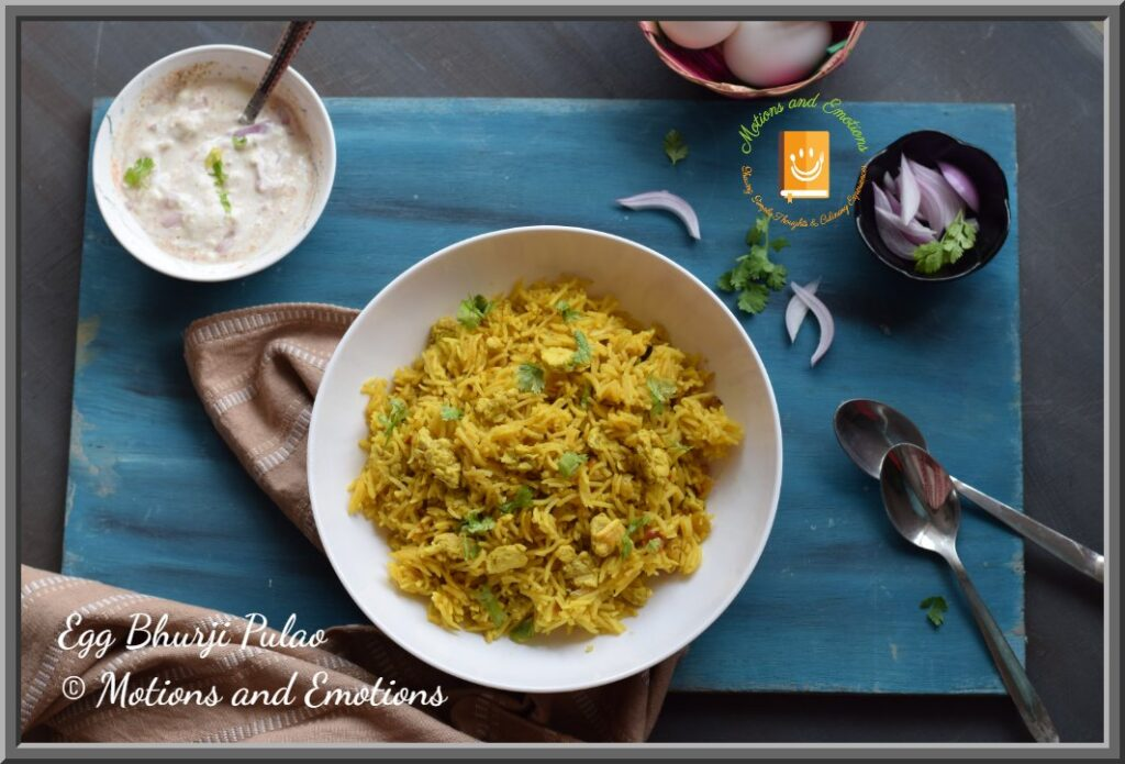 Egg Bhurji Pulao served in a white bowl along with raita and sliced onions