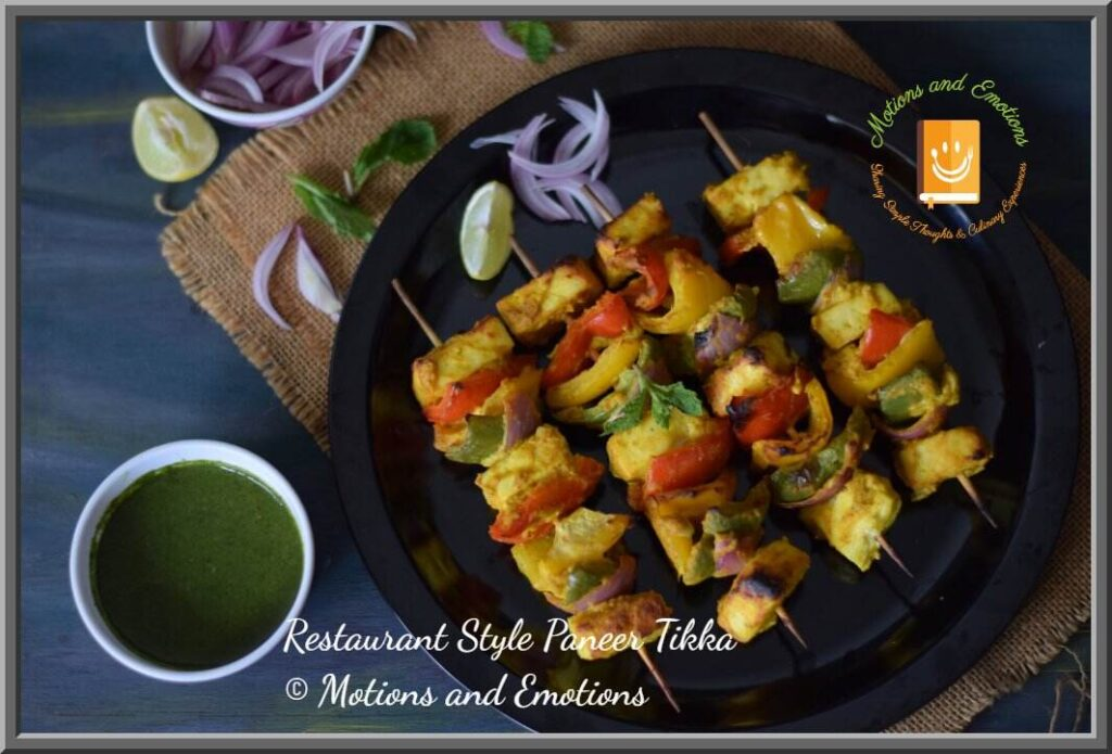 Paneer tikka skewers served on a black plate along with green chutney , top view