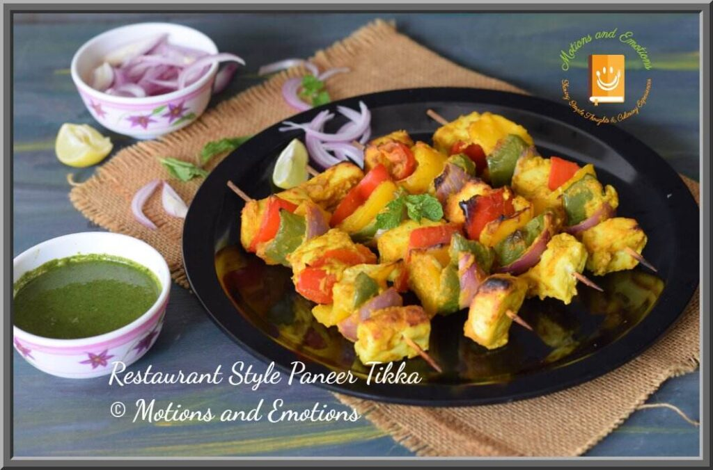 Paneer tikka skewers on black plate along with green chutney and onion slices
