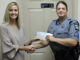 Amanda Formyduval presents Sgt. Pam Bryan with a check from the Good Shepherd Fund.