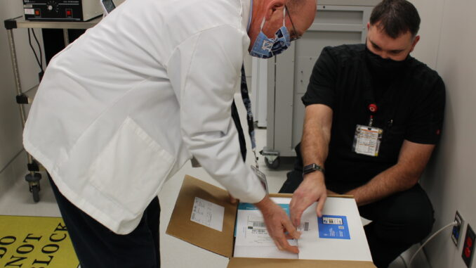 UNC Health Southeastern Pharmacy Director Eric Locklear and Pharmacist Brett Duncan unpack the first COVID-19 vaccines at Southeastern. (Submitted)