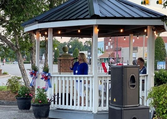 Lori Harper sings for the crowd at Monday's ceremony in Tabor City.