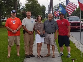 Mitch Simmons, Gray Rogers, Charlotte and Mike Hollingsworth, and Mike Fishburn take a moment while erecting the dozens of flags along Flemington Drive Thursday.