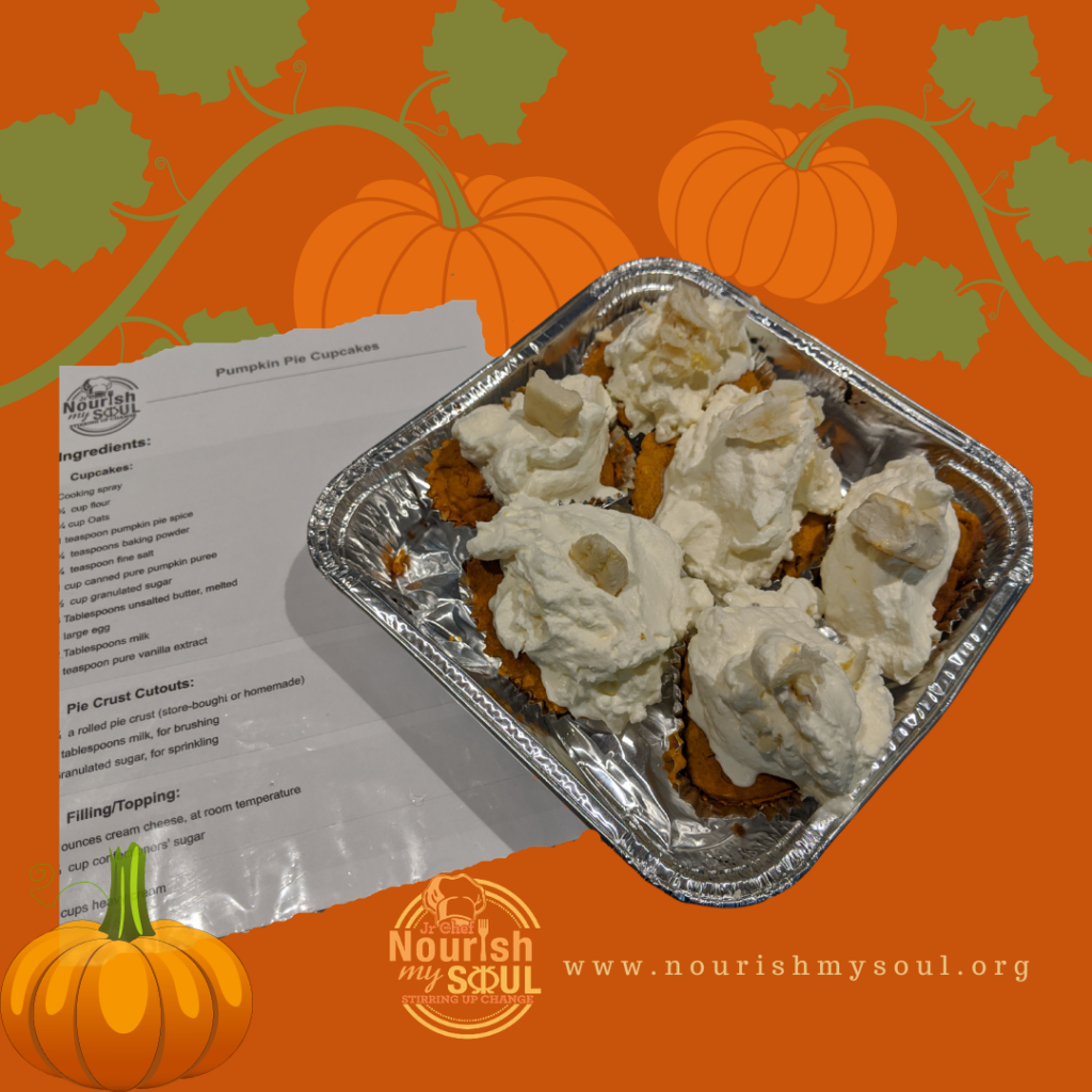 Tin filled with cupcakes topped with whipped cream frosting, a recipe beside it, and pumpkins in the background