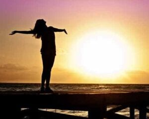 Woman doing sun salutations at sunrise