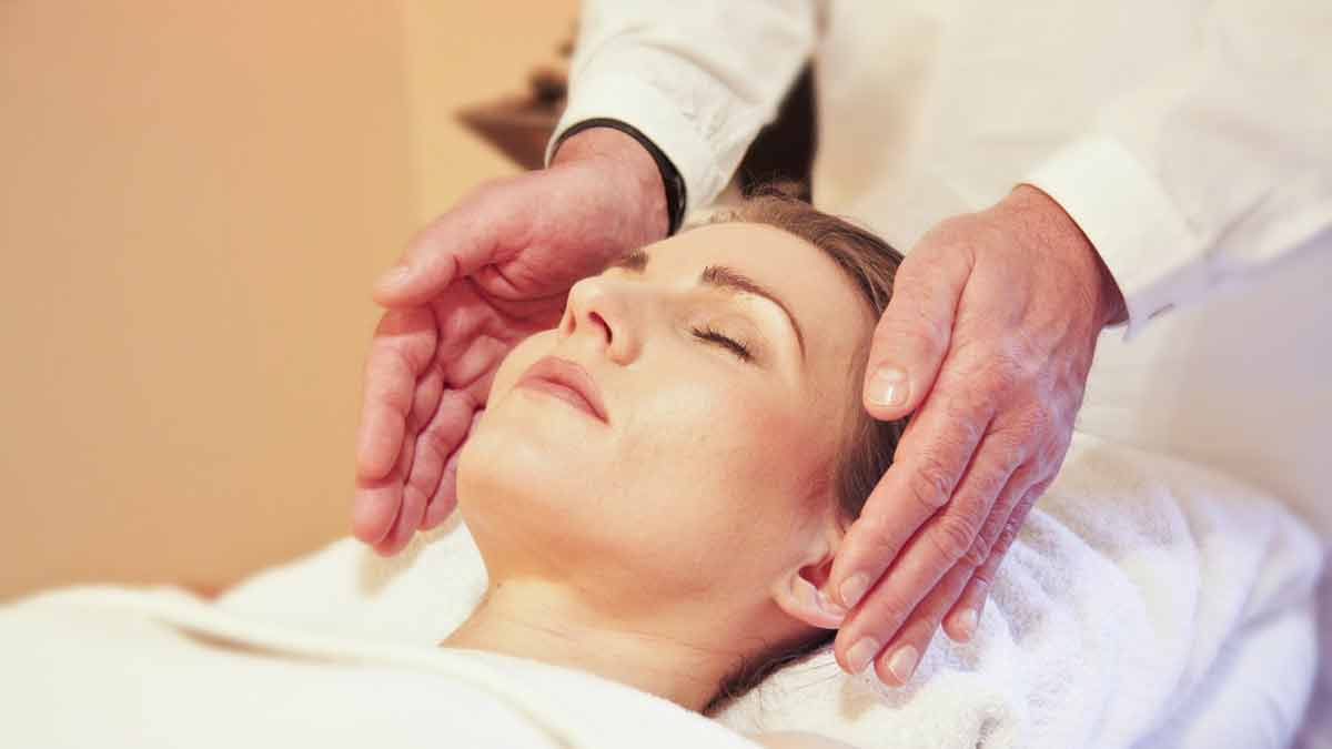 What is Reiki? - woman with her eyes closed receiving Reiki on the sides of her head