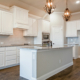 White kitchen cabinets with wood vent hood