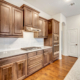Kitchen with wood vent hood and medium stain