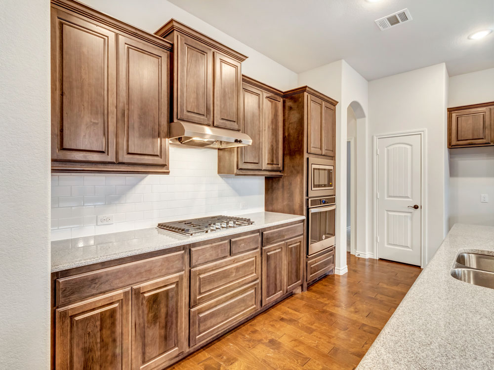 CabSpec kitchen with wood vent hood and medium stain