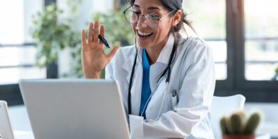 Shot of female doctor waving and talking with colleagues through a video call with a laptop in the consultation.