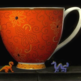 Oil painting by Joanna Strong of a cup of tea or coffe and two miniature dragons.