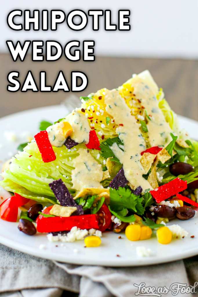 A wedge of iceberg lettuce with corn, black beans, cilantro, green onion, a lime wedge, queso fresco, tortilla strips and creamy chipotle tomatillo dressing.