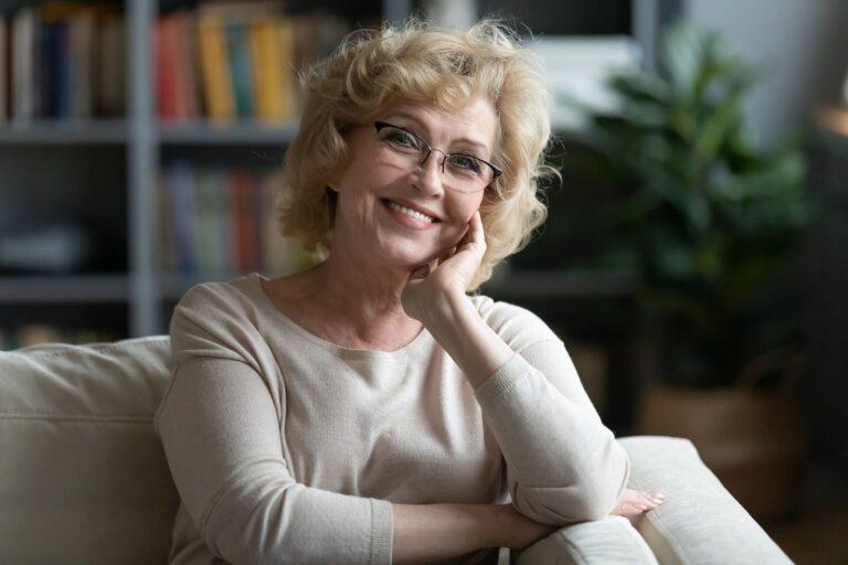 Headshot portrait of happy senior woman rest on couch