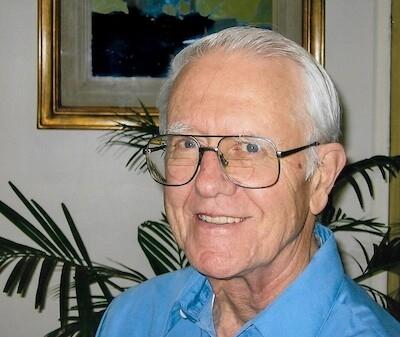 Photo of John Carlson, wearing blue shirt and glasses, smiling at camera.  Plant and painting behind.
