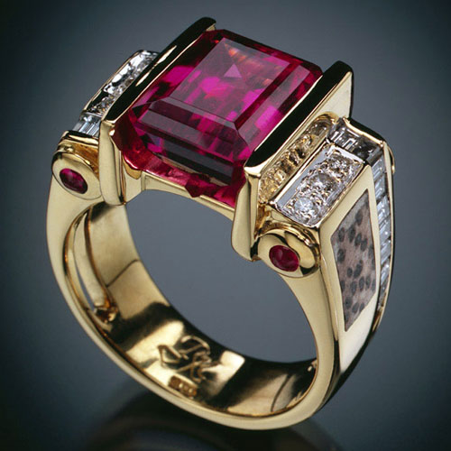 Spectacular 8 Ct emerald cut rubellite tourmaline ring, 4 tube set ruby cabochons, inlaid pertrified palm, and 26 diamonds both channel-set and pave.