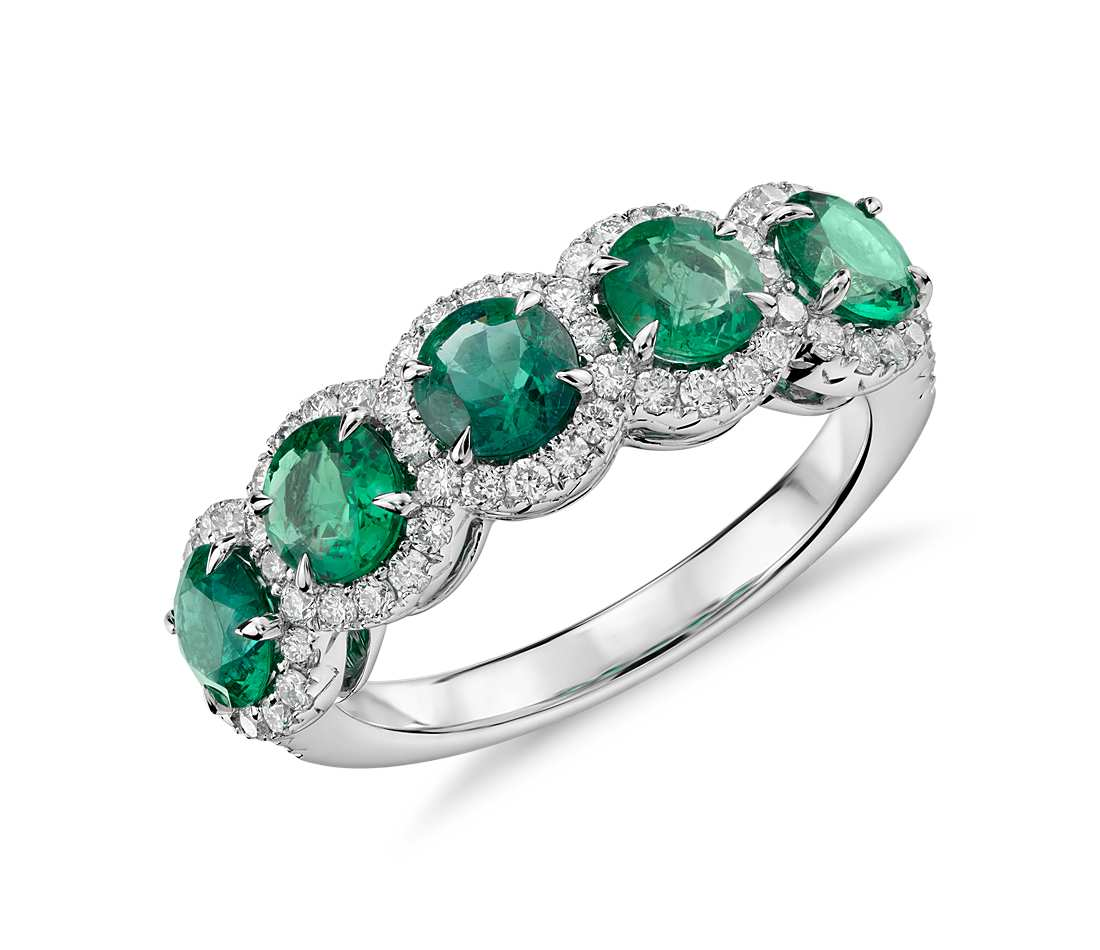 Emerald with Diamond Five-Stone Halo Ring in 18k White Gold (4.5mm) Elegant in design, this ring features vivid green emerald gemstones surrounded by a halo of brilliant diamonds framed in 18k white gold. Due to their delicate nature, emeralds require special care. Removal of this ring when active will maintain beauty and ensure every piece endures for years to come. $5,200