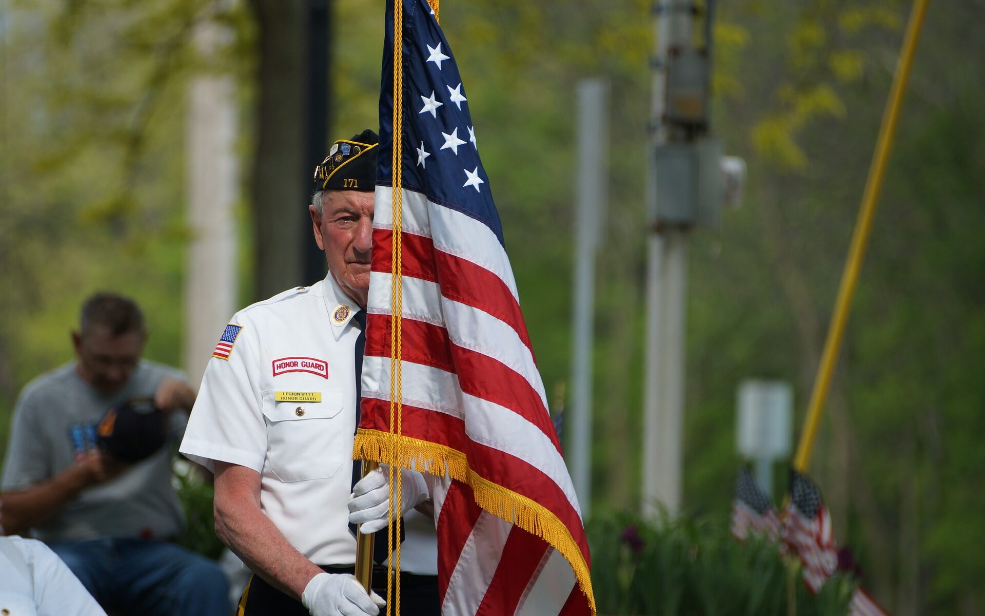 old veteran standing behind american flag at memorial day ceremony