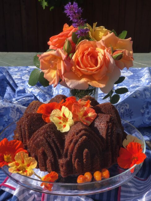 citrus olive oil bundt cake on a platter decorated with flowers