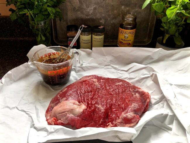 meat marinade ready to be poured on a piece of raw steak