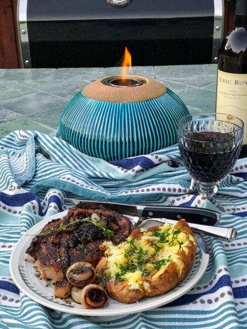 red wine Cipollin onions over steak with baked potato and glass of red wine