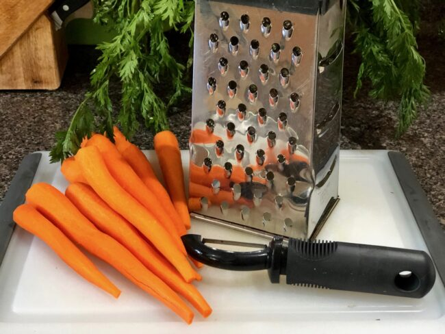 peeled carrots next to a grater