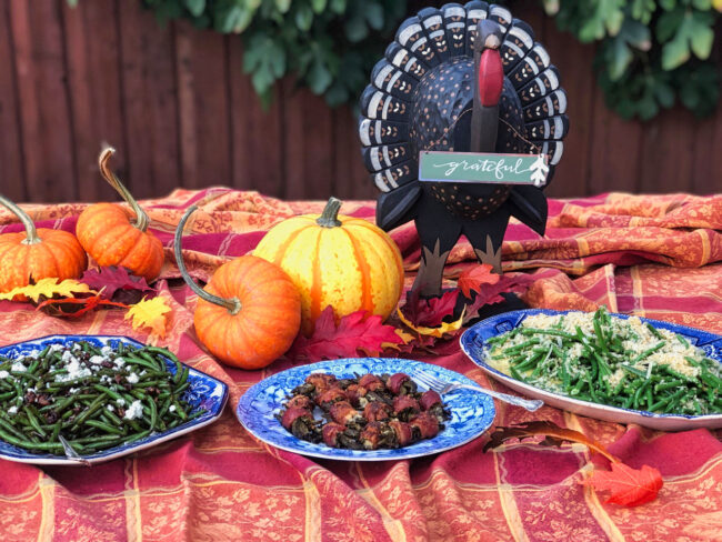 green bean bacon bundles spread on a table with fall decorations