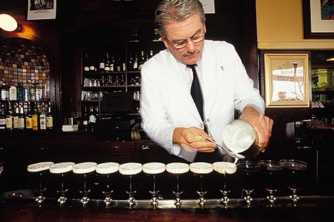 Bartender topping off whipped cream on Irish Coffee