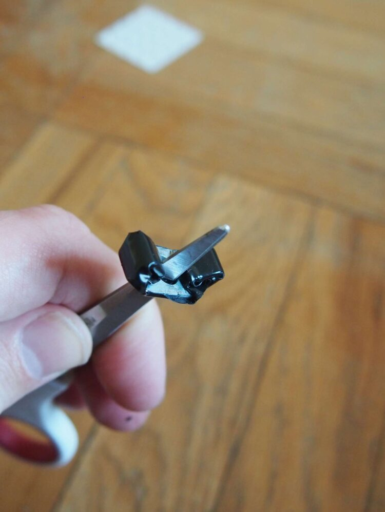 5   Steps 3-5 are for black bookends only. With scissors or an object with a point, poke through the tape where the screw's hole is.