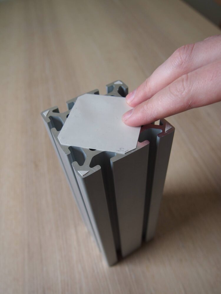 4   Peel the backing off of the rubber square and place the square on the end of the aluminum framing where you sanded. Press down on the rubber to make sure all of the large cavity is covered and sealed.