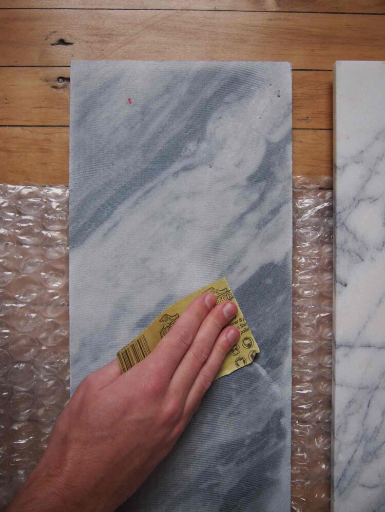 1   Place the tiles on a soft surface and sand any markings off of the rough side of the tile. Wipe with damp cloth.