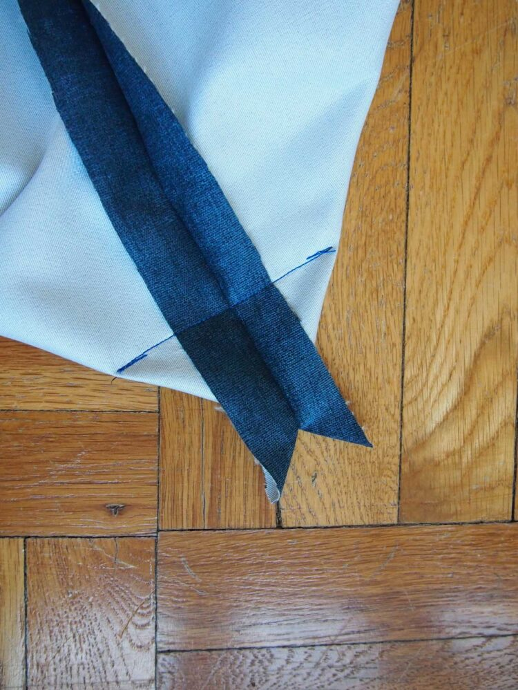 19   Take one corner and line up the seams so that they are exactly in the middle of the corner. Sew across, as pictured, so that your sewing line is exactly 5in (13cm) long from one end of the fabric to the other.