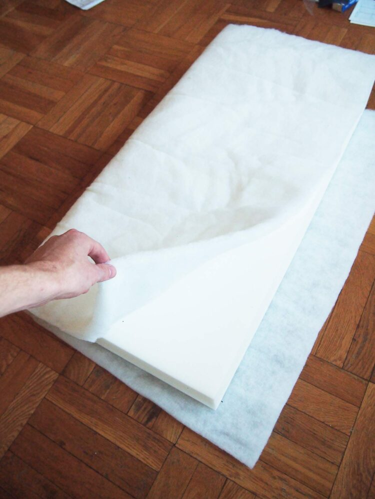 21   Cut out pieces of batting that wrap fully around the length of the foam cushions, as pictured. The batting should not cover much, if any, of the shorter sides of the cushion, as pictured.
