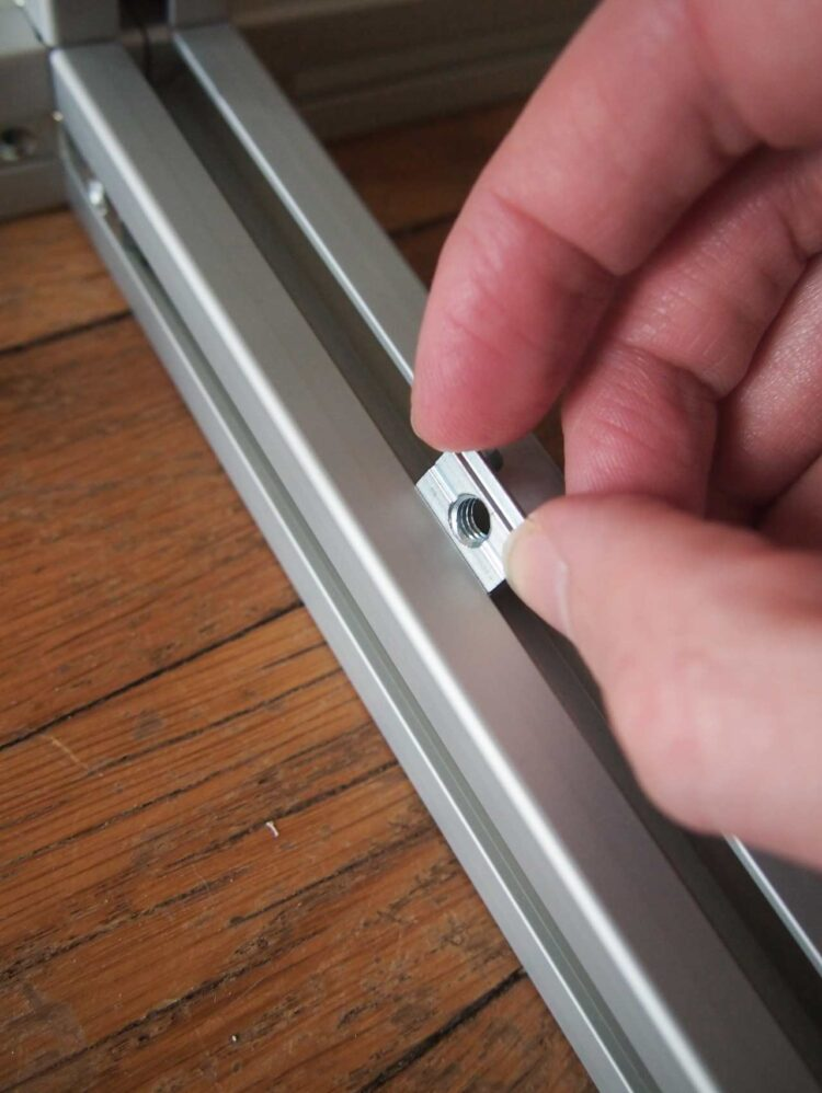 3   To attach the large brackets to the frame, first slide the spring-loaded nuts in place as pictured.