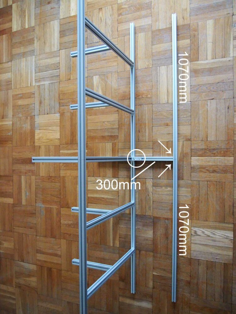 9   Tilt the frame you have assembled so far on its side, and place two 1070mm pieces and one 300mm pieces next to the frame as pictured. Secure them with two small brackets (see arrows) and one large bracket (see circle).