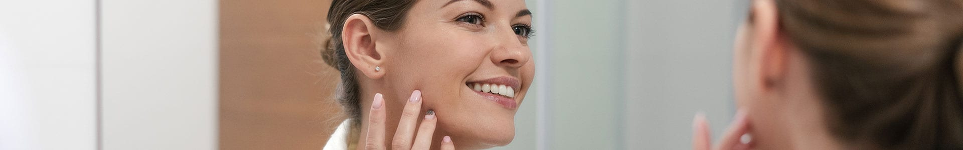 woman looking in the mirror at her skin smiling