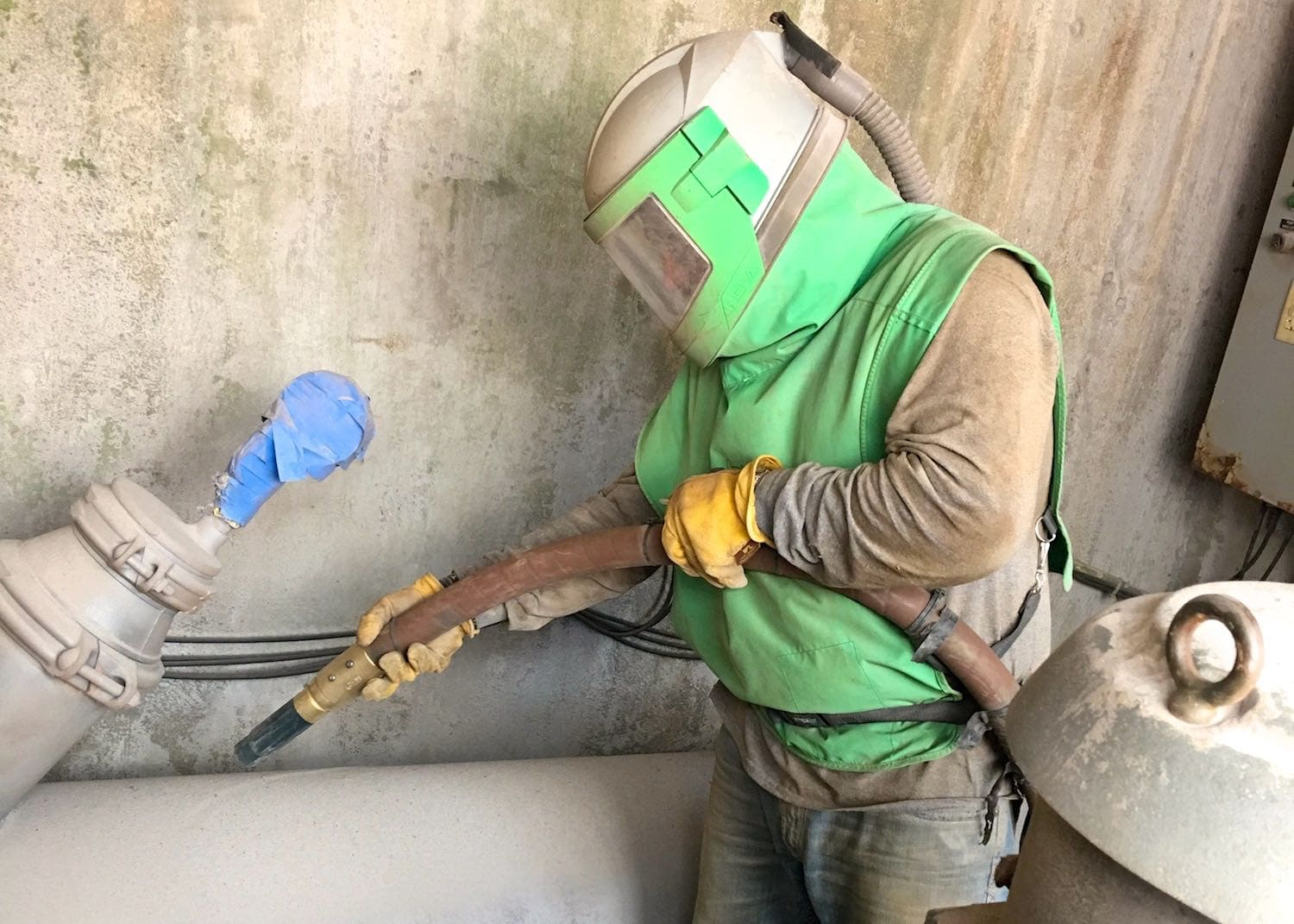 Contractor completing a sand blasting job.