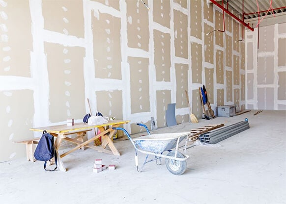 Drywall installation project in an empty room.
