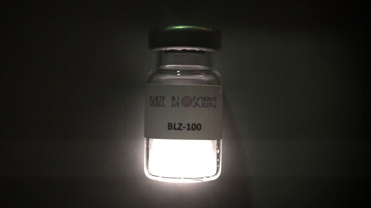 [image: an illuminated medical vial of glowing white liquid, labeled Blaze Bioscience BLZ-100.]
