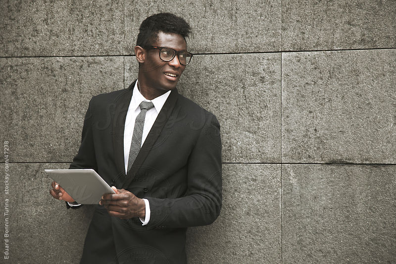 African young businessman standing on a wall with a tablet