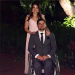 A man in a suit on a wheelchair with a woman in a pink dress