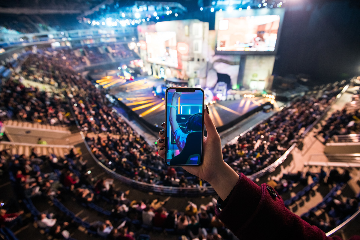 Woman's hands using digital application on the mobile smart phone at esport event at big arena