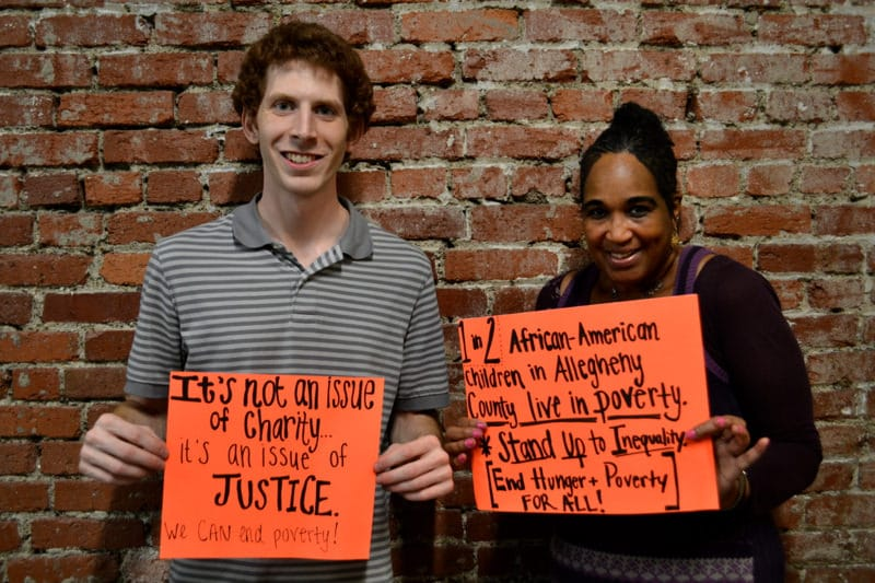 Just Harvest staff Josh Berman and client holding signs about poverty and hunger in Allegheny County