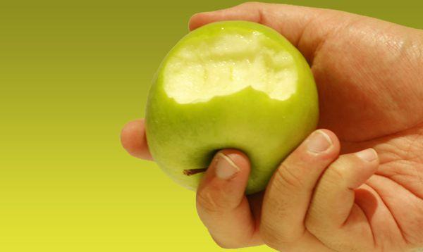 hand holding a bitten green apple