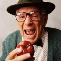 elderly man biting apple