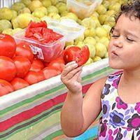 girl tasting tomato at farmers market