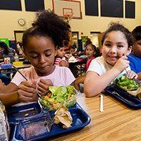 elementary school children eat lunch in cafeteria