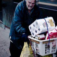 older man pushing groceries (via Flickr/Christos Tsirbas)