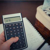 hand holding calculator, stack of bills