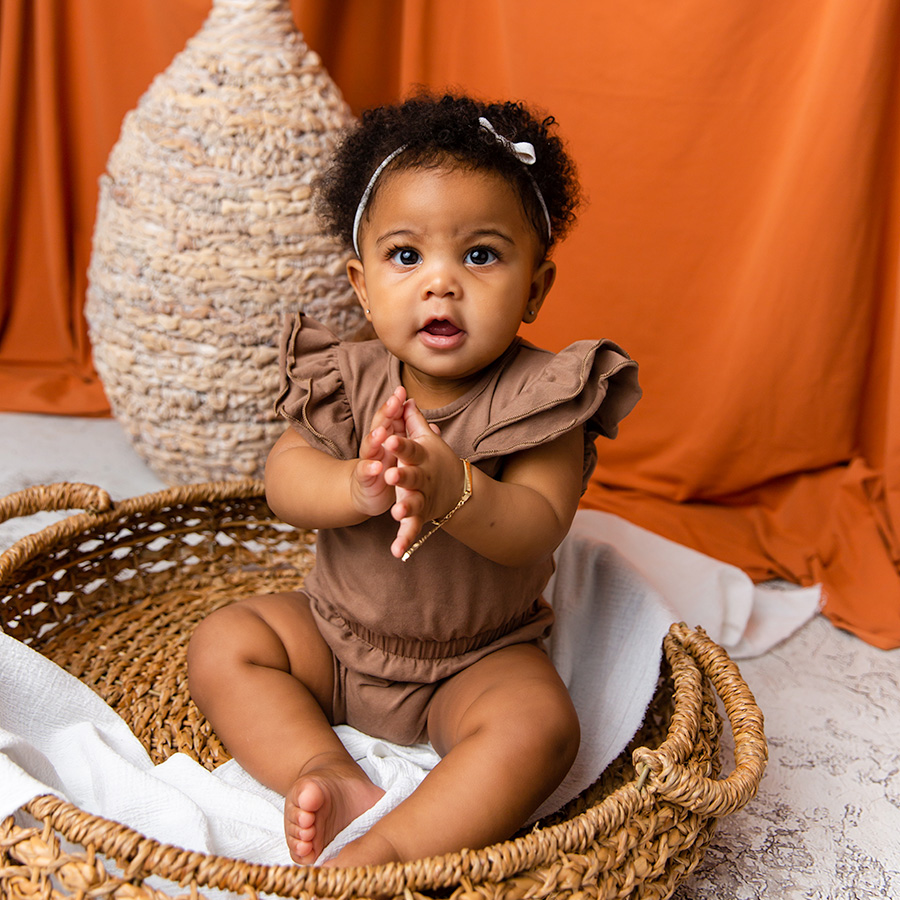 baby girl clapping hands and sitting in basket
